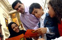 A young Arab family looking at Lion King leaflet