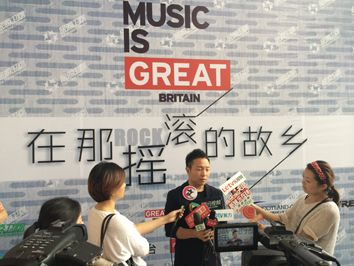 Man being interviewed by broadcast media in front of a VisitBritain Music is GREAT branded media wall