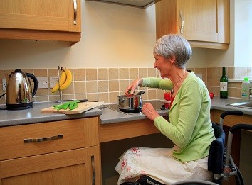 a lady in a wheelchair cooking in a High Wray kitchen