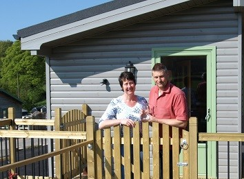 David and Felicity of Hoe Grange Holidays standing outside one of their lodges