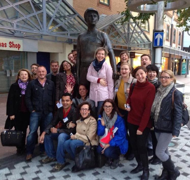 Group shot of staff gathered around a statue at an off site event