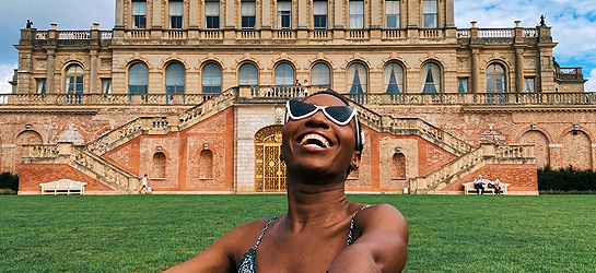 A woman in sunglasses laughing in front of Cliveden House, Berkshire
