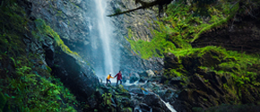 Two people crossing a waterfall in the Scottish Highlands.