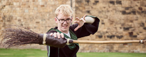 Boy dressed as harry potter playing with a broomstick