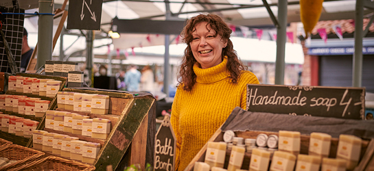 Smiling woman selling handmade soaps at a market in York, North Yorkshire, England.