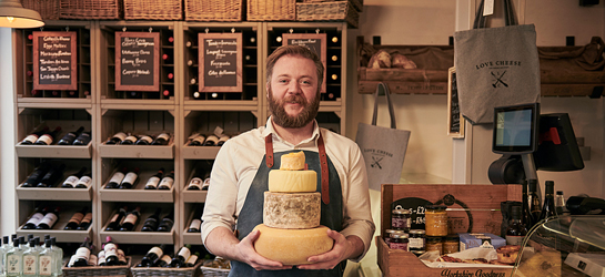 Smiling bearded man wearing blue apron holding stack of cheeses, standing in a cheese shop in York, North Yorkshire, England.