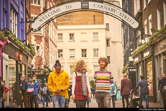 three people walking down Carnaby Street in London, smiling, with shoppers in the background. The sign welcome to Caraby Street can be seen in the mid-distance