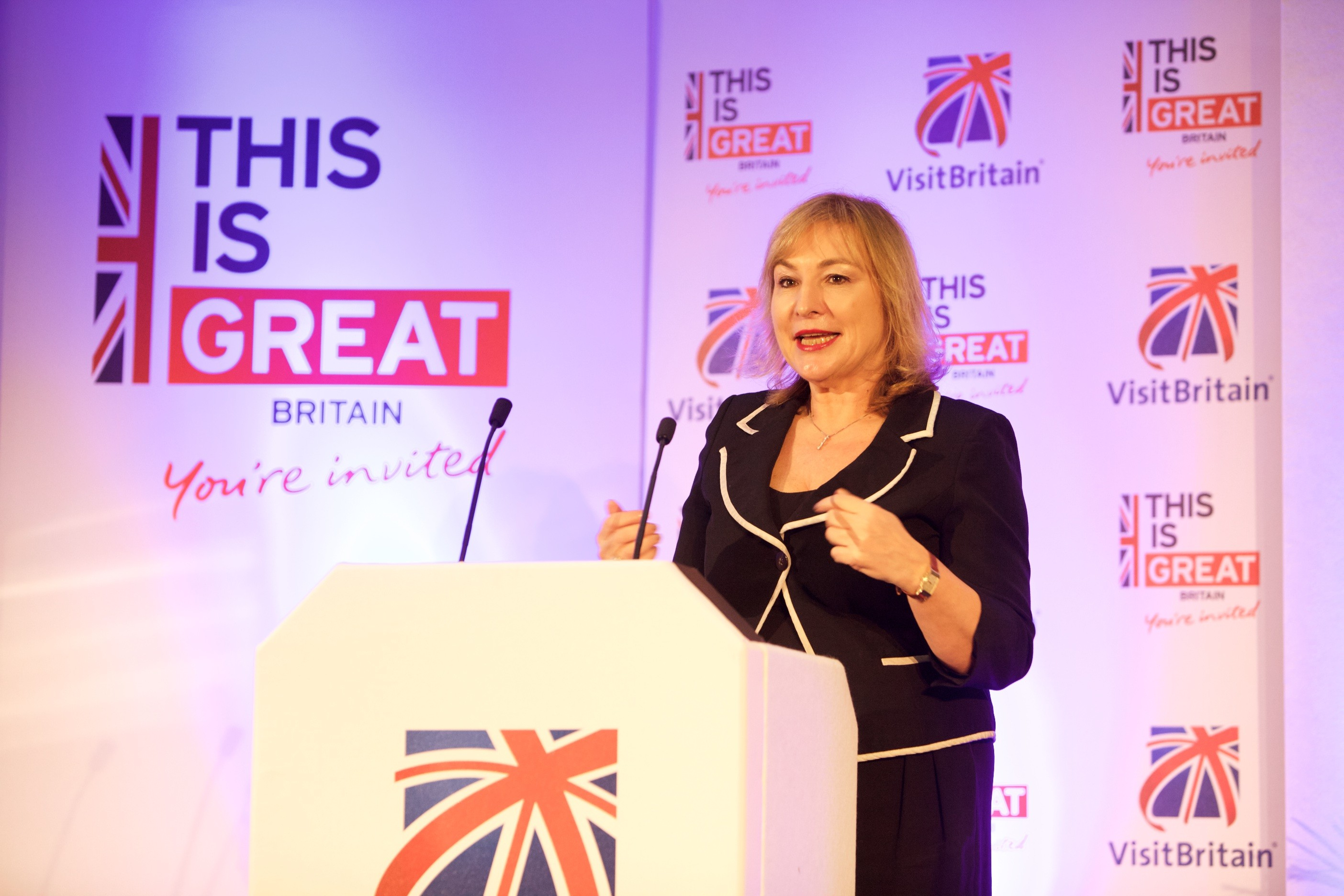 Strategy & Communications Director Patricia Yates delivering a speech in front of a This is GREAT and VisitBritain branded media wall