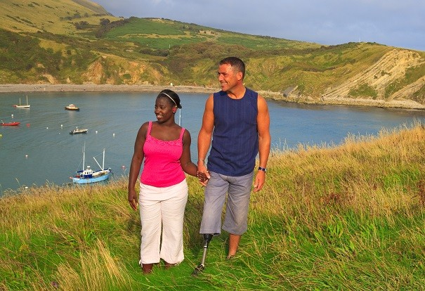An amputee and a friend walking on the Dorset coast