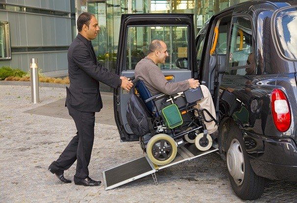 A man in a wheelchair getting into a taxi